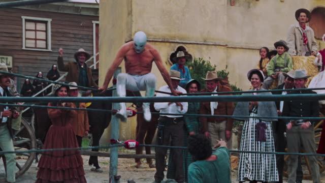 vídeos y material grabado en eventos de stock de el santo wrestlers on a fighting ring with another man in a small village in mexico people including nuns are watching the fight - 1970