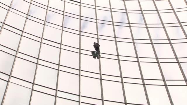 vídeos y material grabado en eventos de stock de el spiderman frances alain robert escalo el sabado sin ningun equipo de seguridad y sin autorizacion un rascacielos de francfort tras lo cual fue... - equipo de seguridad