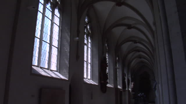 elaborate arches ceilings window along a long hallway in a medieval christian church in germany - 典禮 個影片檔及 b 捲影像