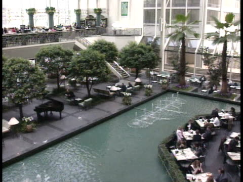elaborate, luxurious dining hall, w/ long fountain, pool, & trees, & second floor balcony seating area, unidentifiable people at tables dining.... - pool hall stock videos & royalty-free footage