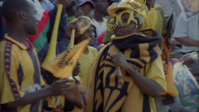 Elaborately dressed Kaizer Chiefs fan moving about crowd and blowing on small horn, Johannesburg Available in HD.