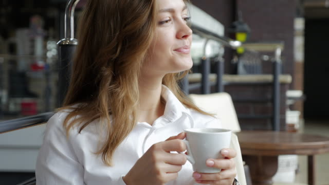 elated brunette with a cup of coffee looking somewhere - coffee cup stock videos & royalty-free footage