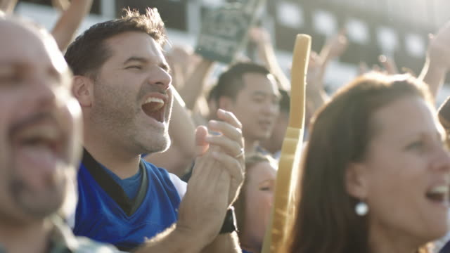 stockvideo's en b-roll-footage met slo mo. elated fans jump to their feet and cheer in crowded football stadium. - vreugde