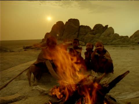 vídeos de stock, filmes e b-roll de elder basarwa tribeswoman and children sitting around campfire in desert at sunset, botswana - tradição