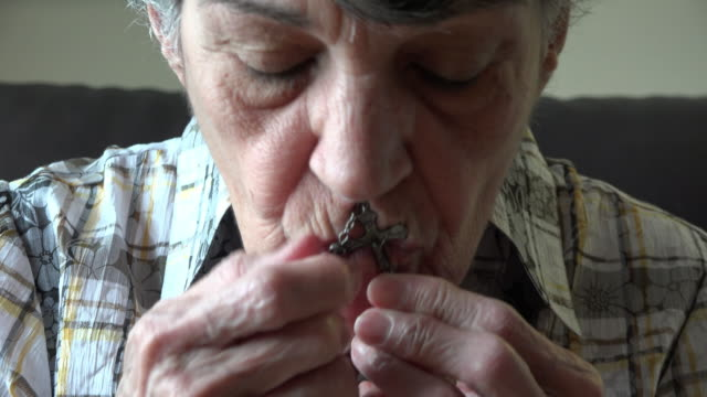 Elder Catholic Senior Woman Praying and Kissing her Rosary