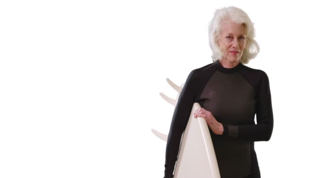 elder caucasian woman holding surfboard looking at camera confidently in studio - old diving suit stock videos and b-roll footage