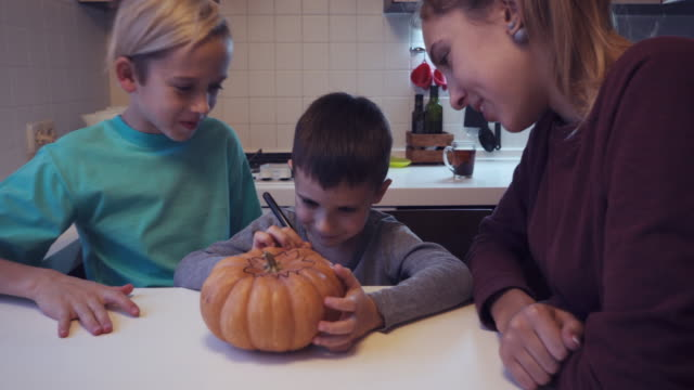 Elder children looking their small brother drawing on pumpkin