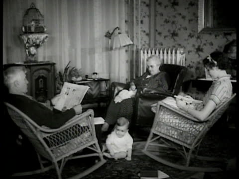 stockvideo's en b-roll-footage met elder couple adult female seated in living room leather rocker wicker rockers embroidering reading baby playing on carpeted floor tall radio radiator... - 1930
