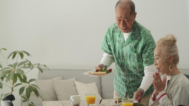 日本人の男性が妻に朝食を持ってくる - 家の中点の映像素材/bロール