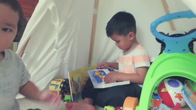 Elder Kid Reading In Tent When Younger Playing With Toys.