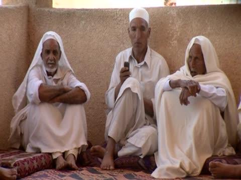 stockvideo's en b-roll-footage met elder men sitting on the floor in zintan - kleding