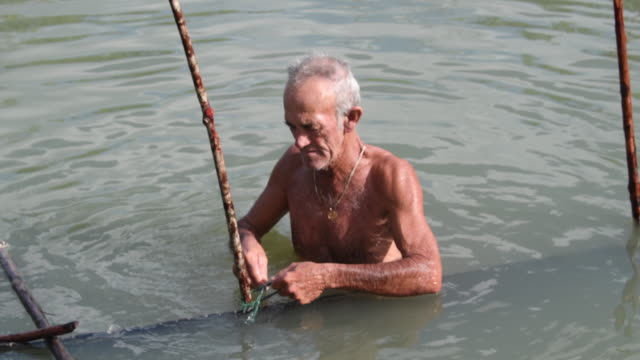 stockvideo's en b-roll-footage met elder or senior man fishing for shrimp in the old way he sets a capturing device after the tide has risen / then he will sleep all night in the open... - steurgarnaal