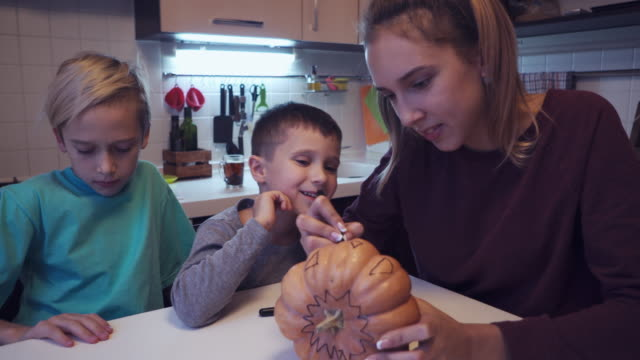 Elder sister teaching small brother to draw on halloween pumpkin