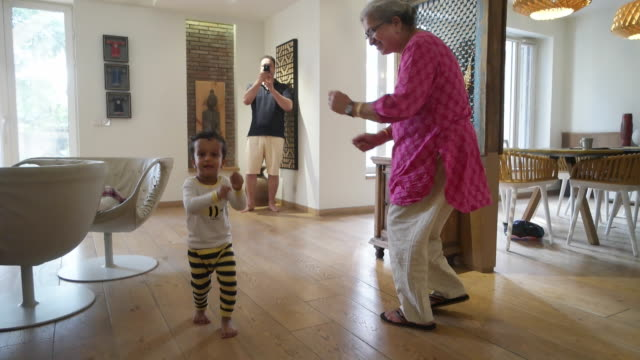 Elder woman dancing with her twin grand children boys, while father making a video