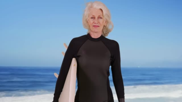 elder woman holding surfboard at scenic beach looking at camera confidently - old diving suit stock videos and b-roll footage