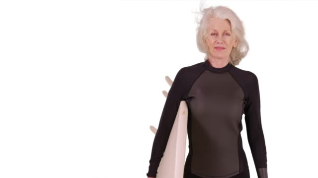 elder woman holding surfboard looking at camera confidently on white background - old diving suit stock videos and b-roll footage