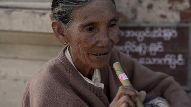 vídeos de stock, filmes e b-roll de elder woman smoking traditional cigar, myanmar - tradição