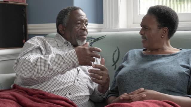 elderly african american couple speak on couch, close up - ehemann stock-videos und b-roll-filmmaterial