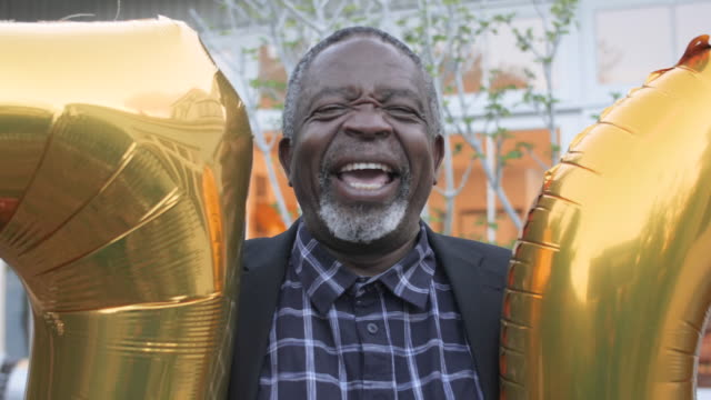 elderly african american laughs while holding birthday balloons, close up - enjoyment stock videos & royalty-free footage