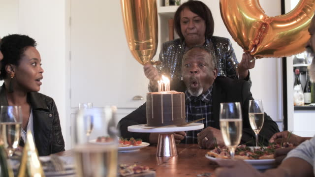 elderly african american man blows out birthday candles, medium shot - birthday candle stock videos & royalty-free footage