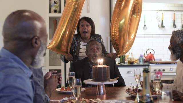 elderly african american man blows out candles, medium shot - birthday gift stock videos & royalty-free footage