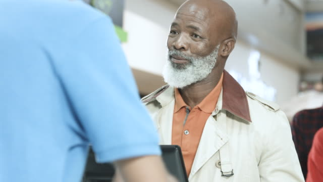 elderly african american man buys movie ticket, close up - checkout stock videos & royalty-free footage