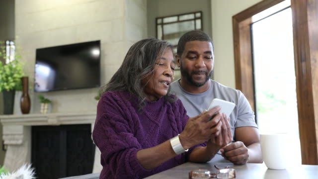 elderly african american woman being assisted by adult son with telehealth visit on smart phone while video conferencing doctor - adult offspring stock videos & royalty-free footage