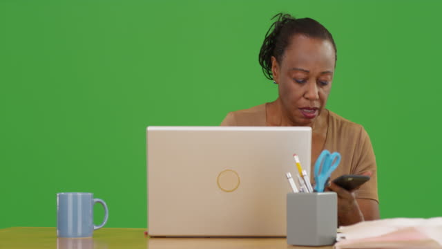 elderly african american woman using her laptop to do her taxes on green screen - maestra video stock e b–roll