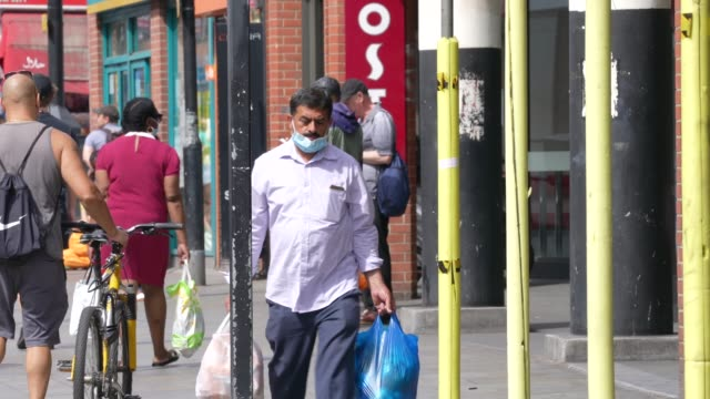 elderly and ethnic minority person wearing ppe face mask in dalston east london during the coronavirus covid-19 pandemic. the british government... - minority groups stock videos & royalty-free footage