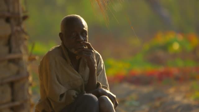 Elderly Angolan man sits outside