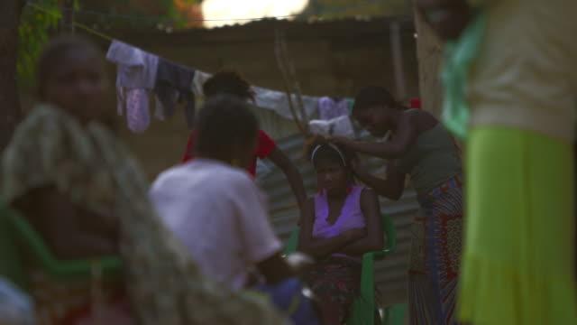 Elderly Angolan women in village sit outside