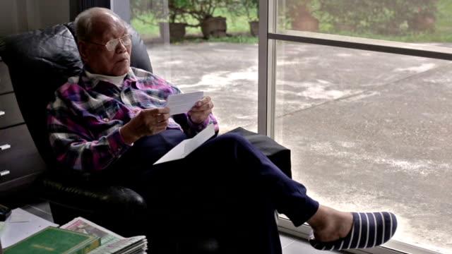 Ältere asiatische Mann liest ein Buchstabe