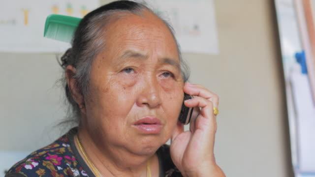 stockvideo's en b-roll-footage met oudere aziatische vrouw praten op mobiele telefoon. - draadloze telefoon