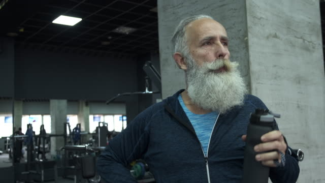 elderly bearded man tries to catch his breath and water drinks in the gym - lap body area stock videos & royalty-free footage