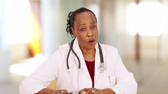 A elderly black doctor cheerfully talks to the camera