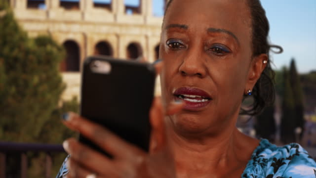 elderly black woman looks at funny pictures of grandchildren on smartphone - african american ethnicity stock videos & royalty-free footage