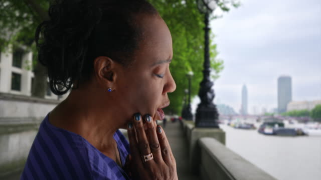 stockvideo's en b-roll-footage met elderly black woman looks sadly at the river thames - weduwe