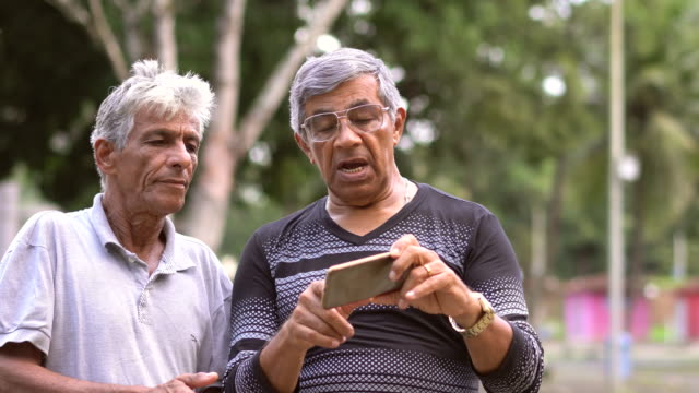 elderly brothers using smart phone - 70 79 years stock videos and b-roll footage
