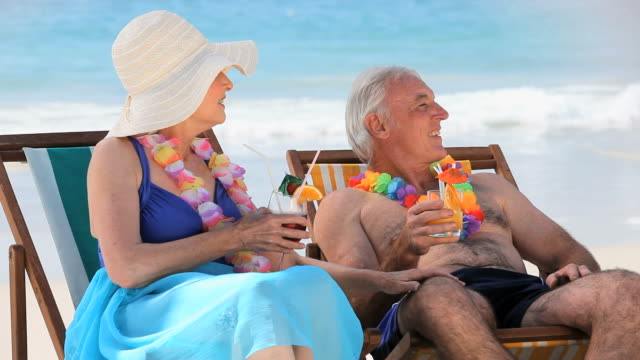 MS Elderly couple drinking cocktails sitting on beach chairs / Cape Town, Western Cape, South Africa