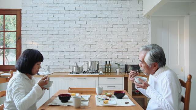 ms elderly couple eating breakfast in kitchen / fujikawaguchiko, yamanashi, japan - asia stock videos & royalty-free footage