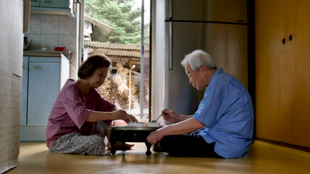 elderly couple eating meal in the kitchen at home - south korea couple stock videos & royalty-free footage
