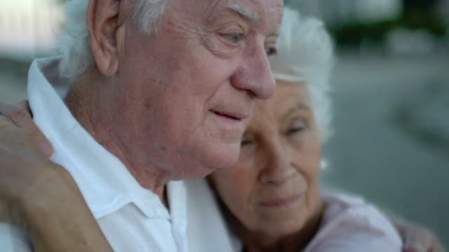 vídeos de stock e filmes b-roll de elderly couple emotionally hugging and smiling at the sunset on the beach - amor