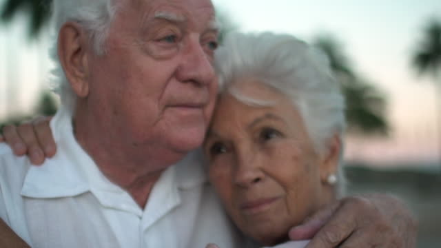 vídeos de stock, filmes e b-roll de elderly couple emotionally hugging and smiling at the sunset on the beach. - sc47
