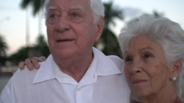 elderly couple emotionally hugging at the sunset.