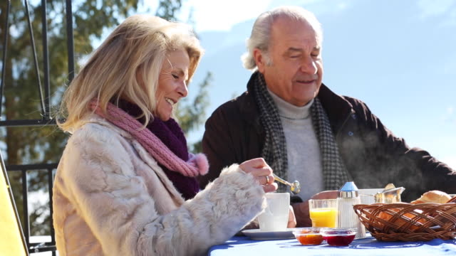 elderly couple enjoying their breakfast in the mountains - cup stock-videos und b-roll-filmmaterial