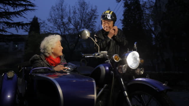 ws elderly couple getting ready to ride a motorcycle with sidecar at night / china - sturzhelm stock-videos und b-roll-filmmaterial