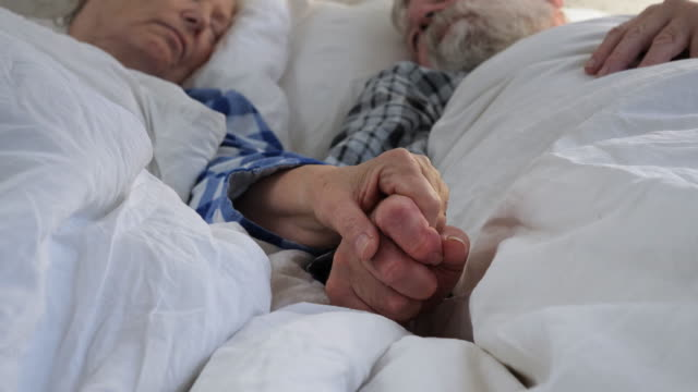 elderly couple holding hands in bed - trust stock videos & royalty-free footage