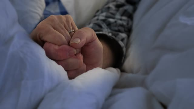 elderly couple holding hands in bed - wellbeing stock videos & royalty-free footage