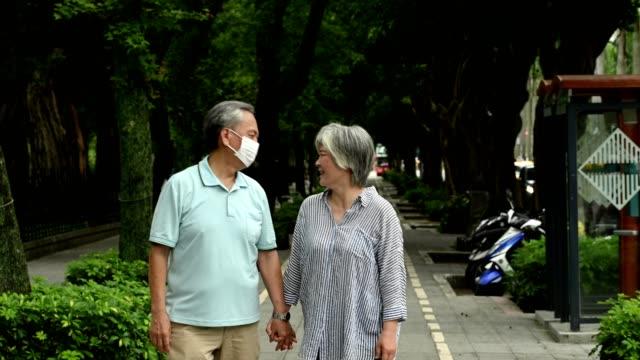 älteres paar hält hände beim gehen im park - zaun stock-videos und b-roll-filmmaterial