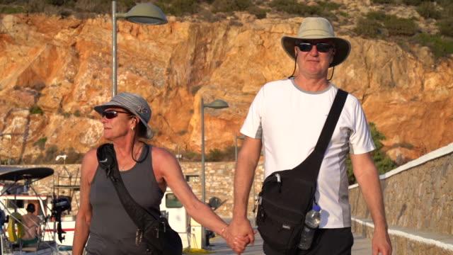 elderly couple holds hands, walks down dock - 65 69 anni video stock e b–roll